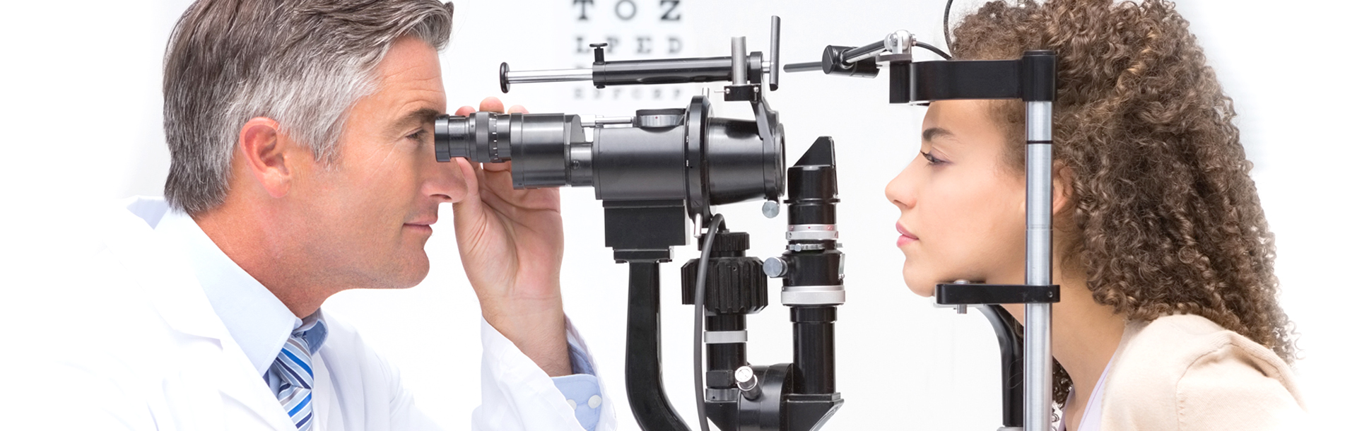 Male doctor viewing female patient's eyes through a slit lamp microscope